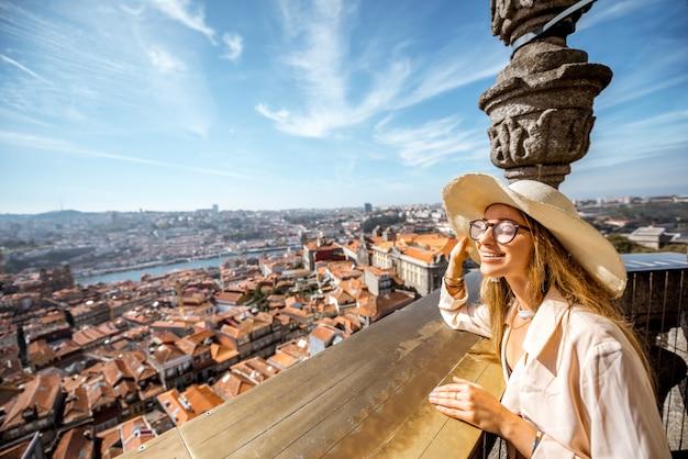 Młoda kobieta turysta podziwiając piękny widok z lotu ptaka z wieży kościoła na stare miasto porto w słoneczny dzień w portugalii