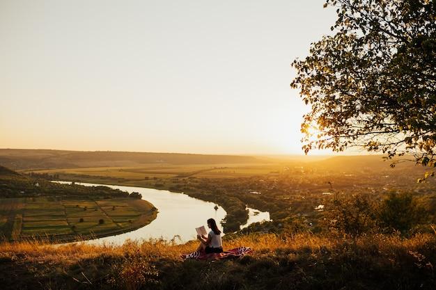 Młoda kobieta turysta siedzi na wzgórzu z rzeką w tle i czytając książkę o zachodzie słońca w górach.