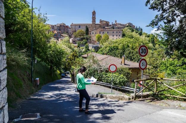 Młoda kobieta turysta studiuje mapę montepulciano w prowincji sienna w toskanii we włoszech