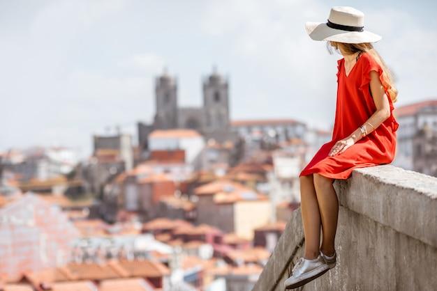 Młoda kobieta turysta w czerwonej sukience siedzi na tle starego miasta podróżując w mieście porto, portugalia