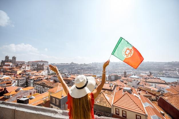 Młoda kobieta turysta w czerwonej sukience stojącej z portugalską flagą na tle starego miasta podróżującego w mieście porto, portugalia