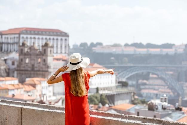 Młoda kobieta turysta w czerwonej sukience stojącej z powrotem na tle starego miasta podróżującego w mieście porto, portugalia