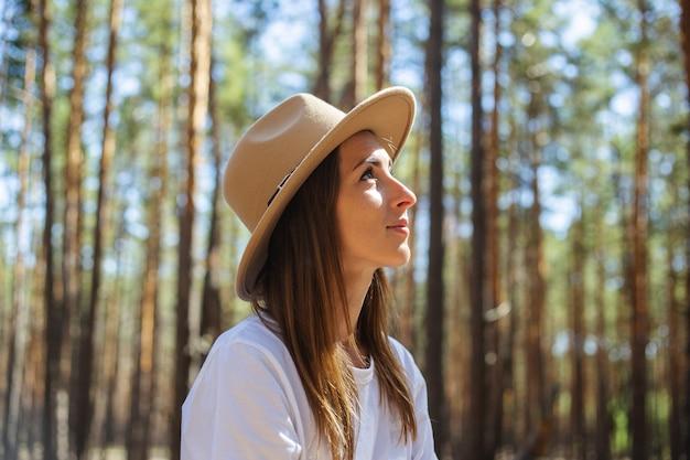 Młoda kobieta turysta w kapeluszu i koszulce podczas postoju w lesie.