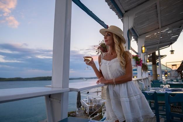 Młoda kobieta turysta w słomkowym kapeluszu siedzi w kawiarni na klifie z widokiem na morze w ermioni greece