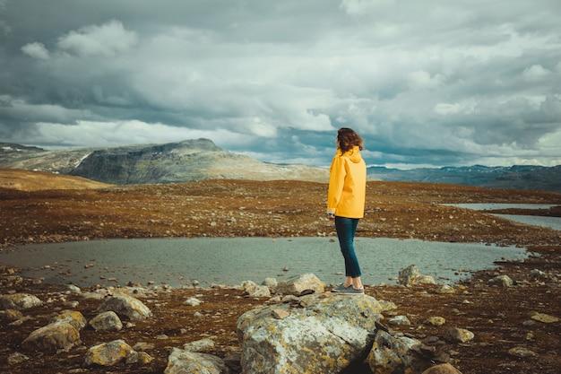 Młoda kobieta turystyczna w żółtej kurtce cieszy się dramatycznym krajobrazem z lodowcowymi jeziorami w norwegii. atmosferyczny krajobraz norweski