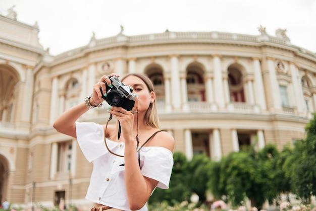 Młoda kobieta turystycznych trzyma w dłoniach aparat retro przeciwko architekturze turystycznego miasta.