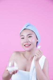 Młoda kobieta twarz maska pad różowy tło.