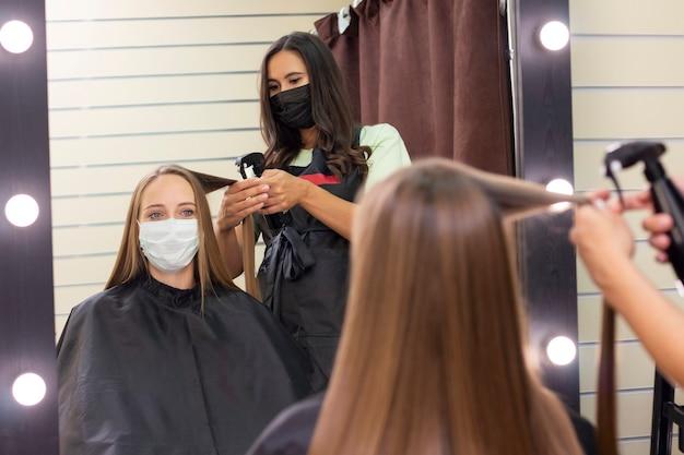 Młoda kobieta u fryzjera na sobie maskę ochronną