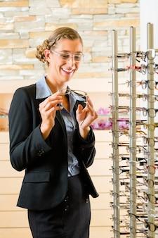 Młoda kobieta u optyka w okularach, może być klientem lub sprzedawcą