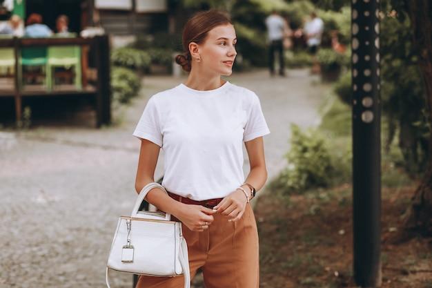 Młoda kobieta ubierał przypadkowego outside w miasto parku