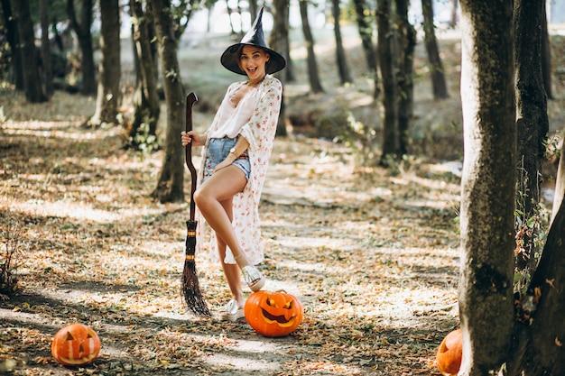 Młoda kobieta ubierał w kapeluszu z miotłą na halloween w lesie
