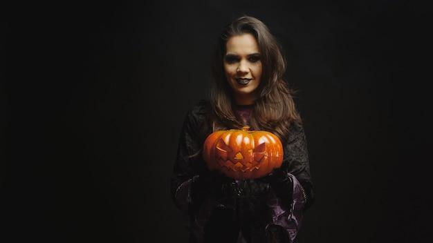 Młoda kobieta ubrana jak wiedźma trzymająca dynię na halloween, patrząc w kamerę na czarnym tle.
