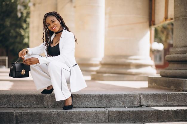 Młoda kobieta ubrana na biało, siedząc na schodach