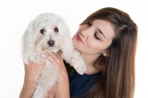 Młoda kobieta, ubrana na niebiesko, z białym psem, przytula ją, obie pozują,