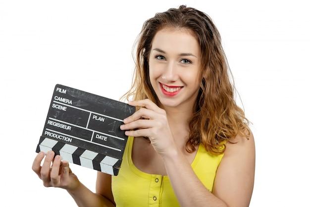 Młoda kobieta ubrana na żółto z grzechotką filmu na białym tle