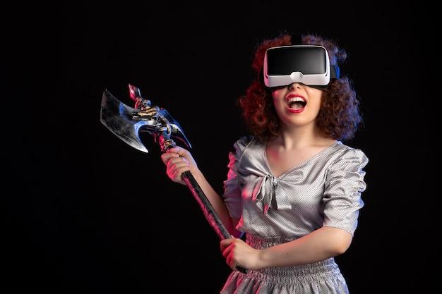 Młoda kobieta ubrana vr zestaw słuchawkowy z toporem bojowym na ciemnej powierzchni