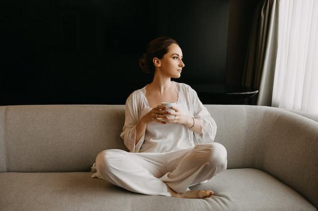 Młoda kobieta ubrana w białą jedwabną piżamę, siedząca na kanapie, trzymając filiżankę kawy.