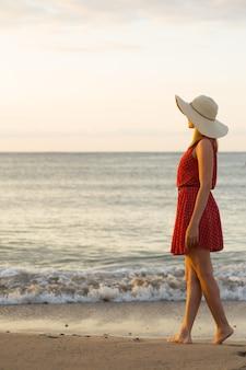 Młoda kobieta, ubrana w biały kapelusz i czerwoną sukienkę, z widokiem na morze.
