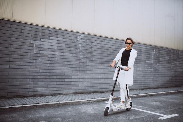 Młoda kobieta ubrana w biały skuter