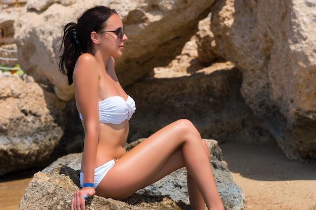 Młoda kobieta ubrana w biały strój kąpielowy i okulary przeciwsłoneczne, siedząca na skale na plaży w słoneczny letni dzień