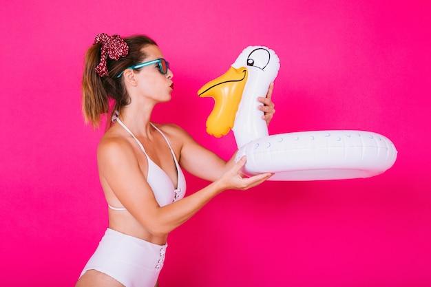 Młoda kobieta ubrana w bikini daje pocałunek pływakowi łabędzia na różowym tle