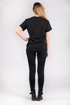 Młoda kobieta ubrana w czarną koszulkę z krótkim rękawem stojącą przy białej ścianie