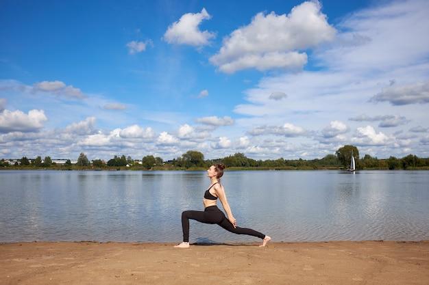 Młoda kobieta ubrana w czarną odzież sportową uprawiania jogi na piasku w pobliżu jeziora.
