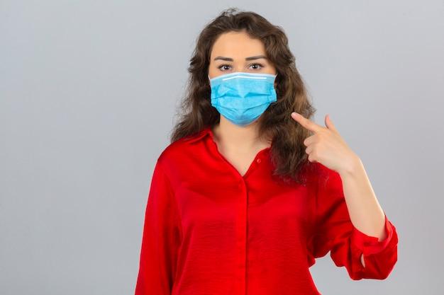 Młoda kobieta ubrana w czerwoną bluzkę w medycznej masce ochronnej patrząc na kamery i wskazując palcem na maskę na twarzy na białym tle