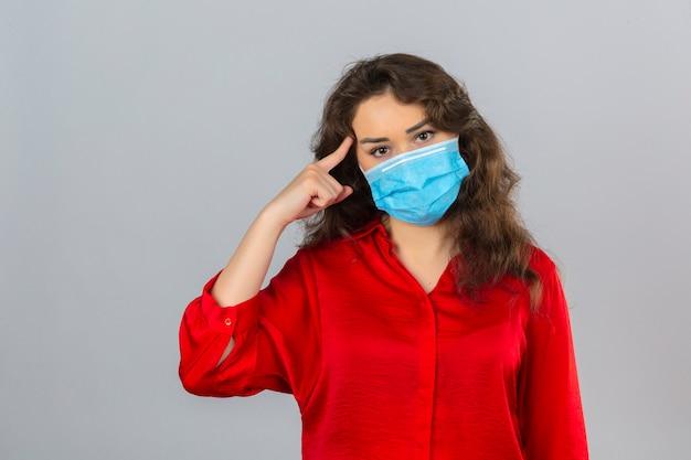 Młoda kobieta ubrana w czerwoną bluzkę w medycznej masce ochronnej patrząc na kamery, wskazując palcem na głowę na na białym tle