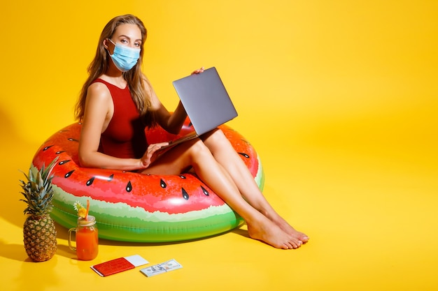 Młoda kobieta ubrana w czerwony strój kąpielowy siedzi na dmuchanym kółku na żółtym tle, ubrana w ...