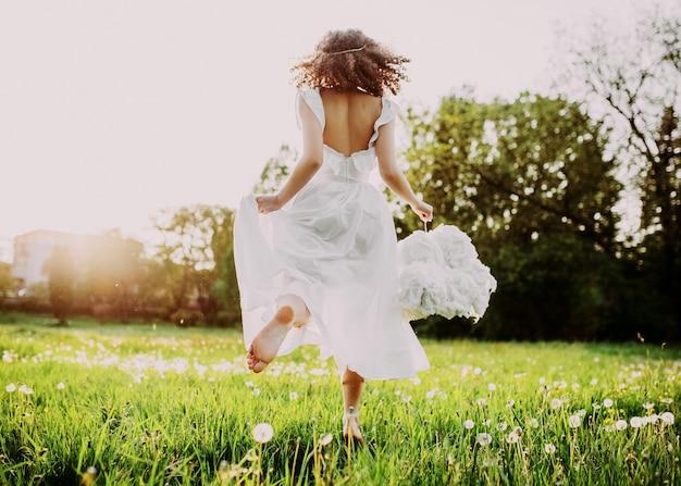 Młoda kobieta ubrana w długą białą sukienkę