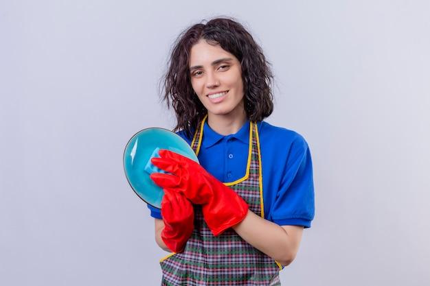 Młoda kobieta ubrana w fartuch i rękawice gumowe mycie talerza z uśmiechem na twarzy na białej ścianie