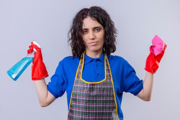 Młoda kobieta ubrana w fartuch i rękawice gumowe, trzymając spray do czyszczenia i dywan, rozkładając ręce z sceptycznym wyrazem twarzy na białej ścianie