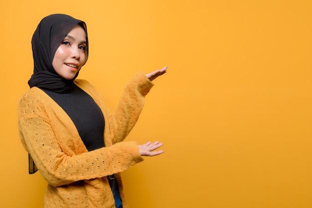 Młoda kobieta ubrana w hidżab pokazuje produkt