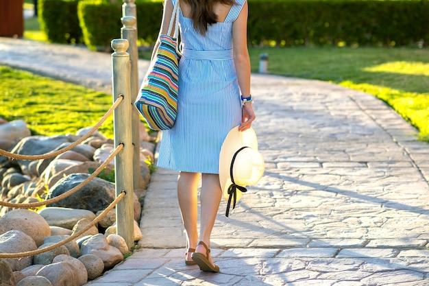 Młoda kobieta ubrana w jasnoniebieską letnią sukienkę, trzymając modną torbę na ramię i żółty słomkowy kapelusz