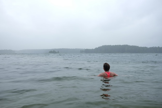 Młoda kobieta ubrana w jasny top pływanie w jeziorze w mglisty deszczowy dzień.
