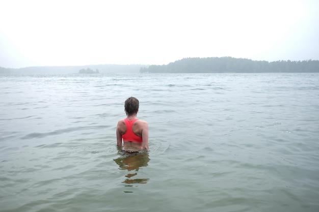 Młoda kobieta ubrana w jasny top pływanie w mglistym jeziorze w deszczowy dzień.