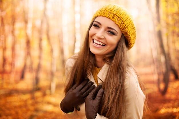 Młoda kobieta ubrana w jesienne ubrania, śmiejąc się w parku