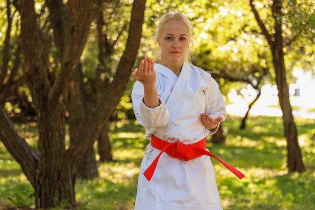 Młoda kobieta ubrana w kimono jej praktykowania karate porusza się w parku - czerwony pas