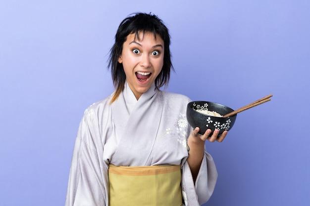 Młoda kobieta ubrana w kimono na pojedyncze niebieskie miejsce z zaskoczenia i zszokowany wyraz twarzy, trzymając miskę makaronu pałeczkami