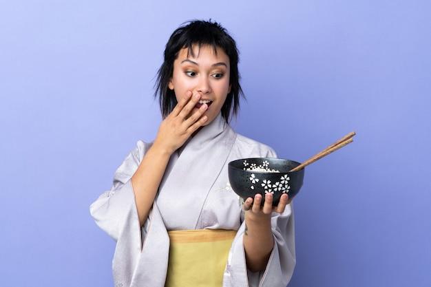 Młoda kobieta ubrana w kimono na pojedyncze niebieskie z zaskoczenia i zszokowany wyraz twarzy, trzymając miskę makaronu pałeczkami
