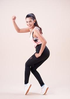 Młoda kobieta ubrana w kombinezon do ćwiczeń, robi taniec, do ćwiczeń