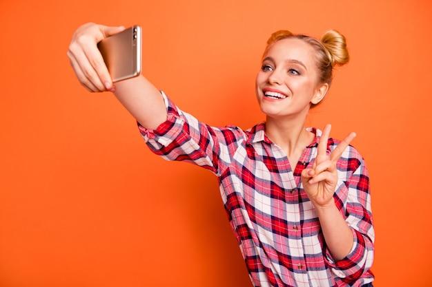 Młoda kobieta ubrana w kraciastą koszulę w kratkę na pomarańczowo ze swoim telefonem