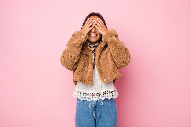 Młoda kobieta ubrana w krótki kożuch zakrywa oczy rękami, szeroko się uśmiecha, czekając na niespodziankę
