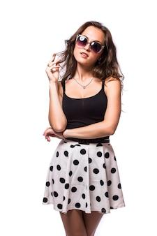 Młoda kobieta ubrana w letnią sukienkę z okularami przeciwsłonecznymi pojedynczo na białym tle