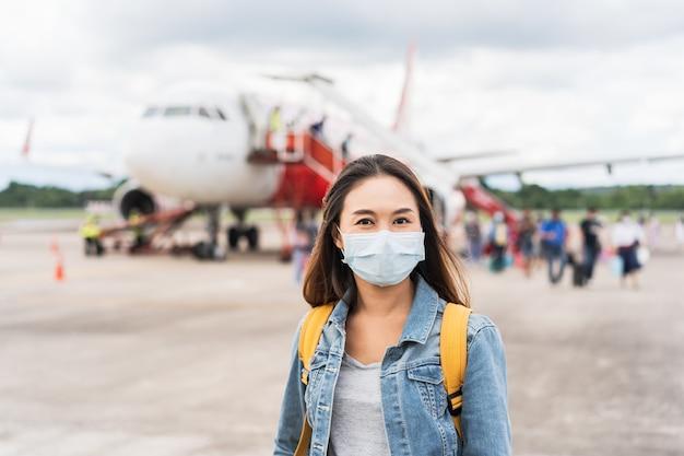 Młoda kobieta ubrana w maskę na lotnisku, nowa koncepcja normalnego stylu życia