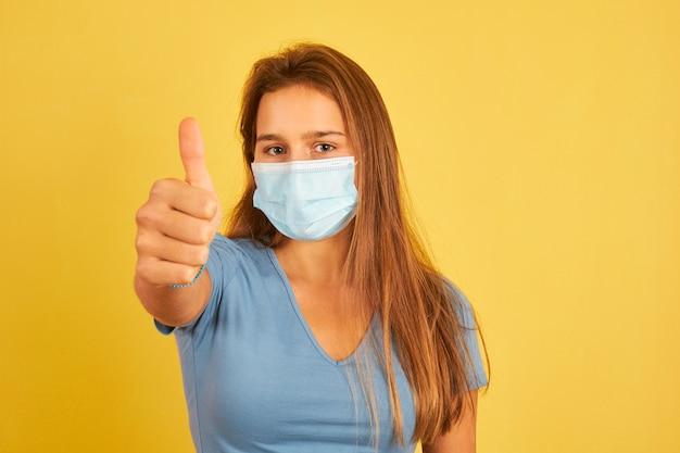 Młoda kobieta ubrana w maskę na żółtej ścianie