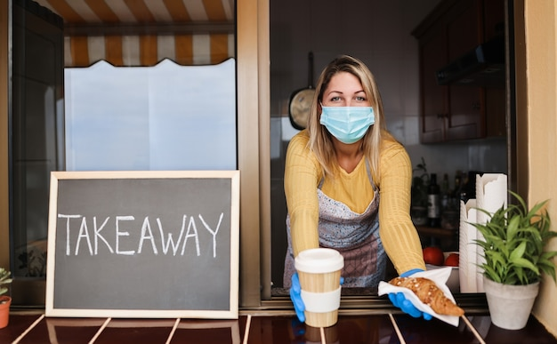 Młoda kobieta ubrana w maskę podczas serwowania śniadania na wynos i kawy wewnątrz kawiarni piekarni