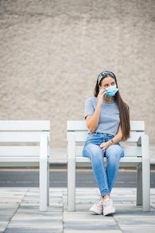 Młoda kobieta ubrana w maskę rozmawia przez telefon