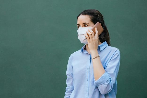 Młoda kobieta ubrana w maskę rozmawia telefon na zielonym tle i kopia przestrzeń po lewej stronie